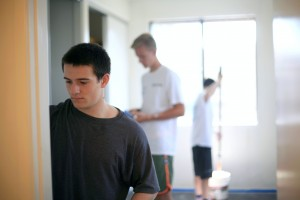 National League of Young Men members Ethan Zimmerman, 16, sophomore at Newport Harbor High School (front), Blake Richter, 15, freshman at NHHS (middle), and Jack Pritchess, 15, freshman at Mater Dei High School, paint one of the rooms at a Human Options housing location last weekend.