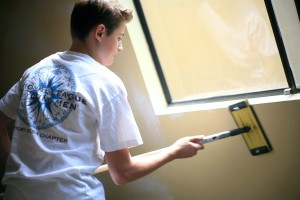NLYM member Aidan Steinke, 14, prepares a room to be painted and refurbished at the safe haven location for women and children in the Human Options program.