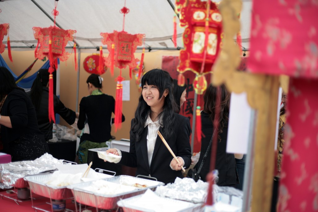Sage Hill School student Dana Shan helps out at the China booth during the school's 13th Annual Multicultural Fair last year. — Photo by Sara Hall