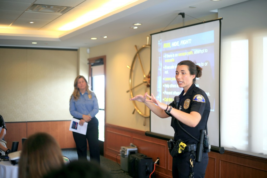 Newport Beach Police Department officer and School Resource Officer Marie Gamble talks about what to do in an active shooter situation while NBPD  Crime Prevention Specialist Andi Querry listens in the background during the Chamber of Commerce's lecture on Wednesday. — Photo by Sara Hall ©