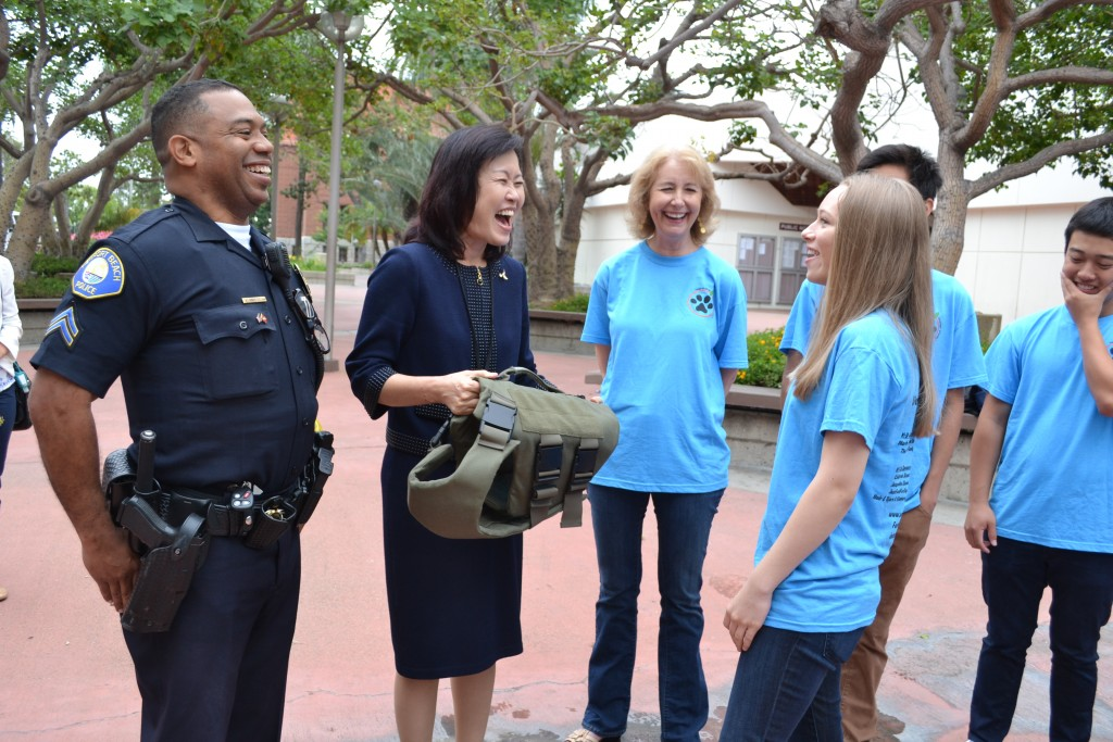 (left to right) Newport Beach Police Department's School Resource Officer for Corona del Mar High School Vlad Anderson, Orange County Supervisor Michelle Steel, CdMHS Vest-A-Dog club staff advisor Tory Hughes, and CdMHS Vest-A-Dog student founder Jenny Conde smile and talk as they look over one of the vests the club buys for local police K-9 officers before the OC Board of Supervisors meeting on Tuesday in Santa Ana.  — Photo by Darla Conde