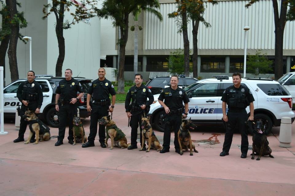 Local police officers and their K-9 partners pose for a photo Tuesday before the OC Board of Supervisors meeting.  — Photo by Darla Conde