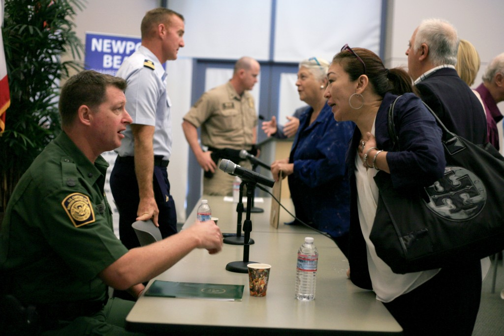 (front left) U.S. Border Patrol agent in charge Mark Dunbar and other Department of Homeland Security officials speak with attendees after the Wake Up! Newport meeting on Thursday. — Photo by Sara Hall ©