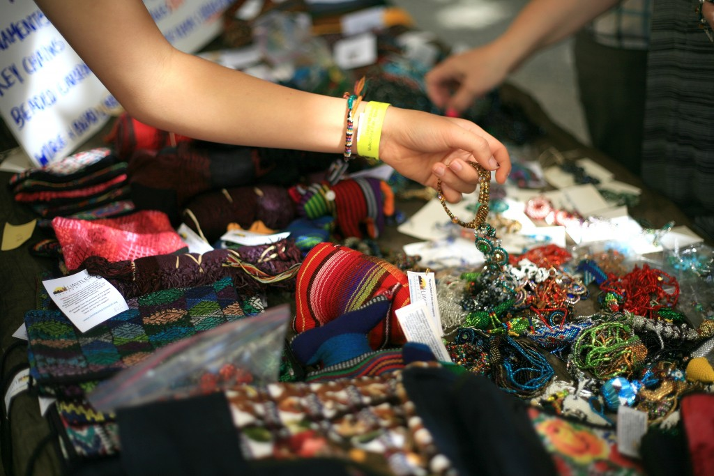Festival guests look through handmade jewelry sold during the event at the ethnic bazaar. Proceeds benefit Limitless Horizons Ixil, a nonprofit that works to create opportunities for the indigenous youth, women, and families of Chajul, Guatemala. — Photo by Sara Hall ©