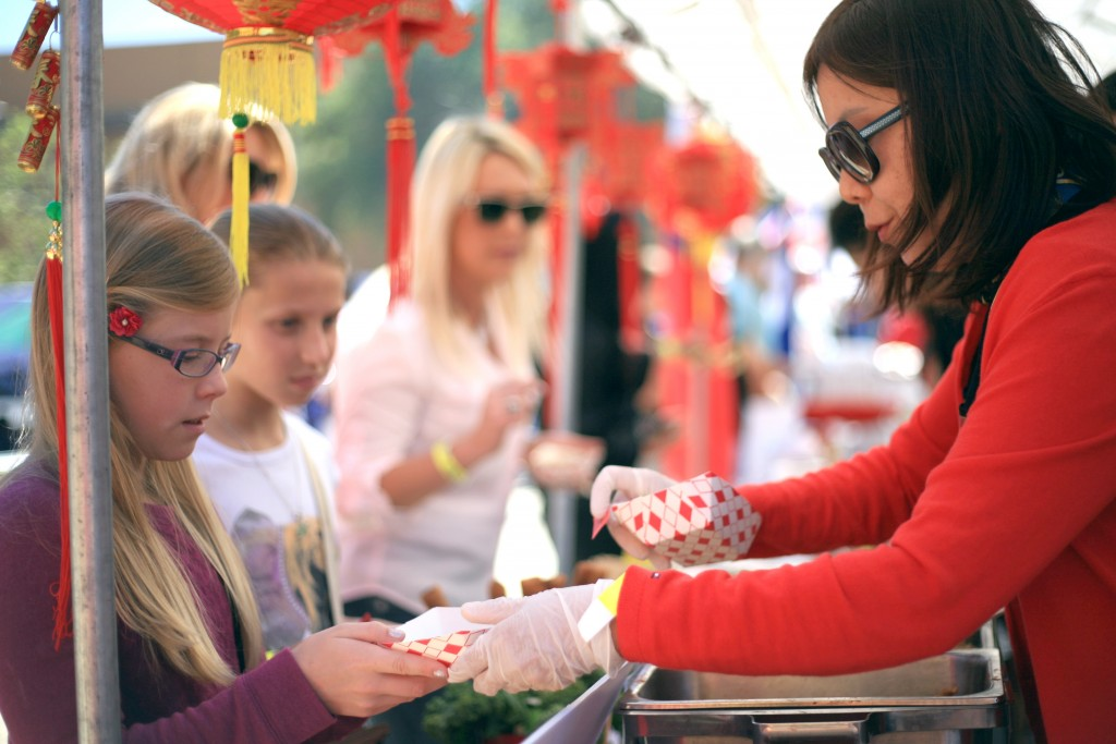 Volunteer mom Terri Wang hands Abigal Richards, 10, and Anika Ball, 11, egg rolls at the China food booth at the festival. — Photo by Sara Hall ©