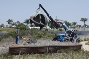 """Workers lower """"Act/Equator Z360"""" by Kenneth Capps into place in the park. Photo by Chris Trela"""