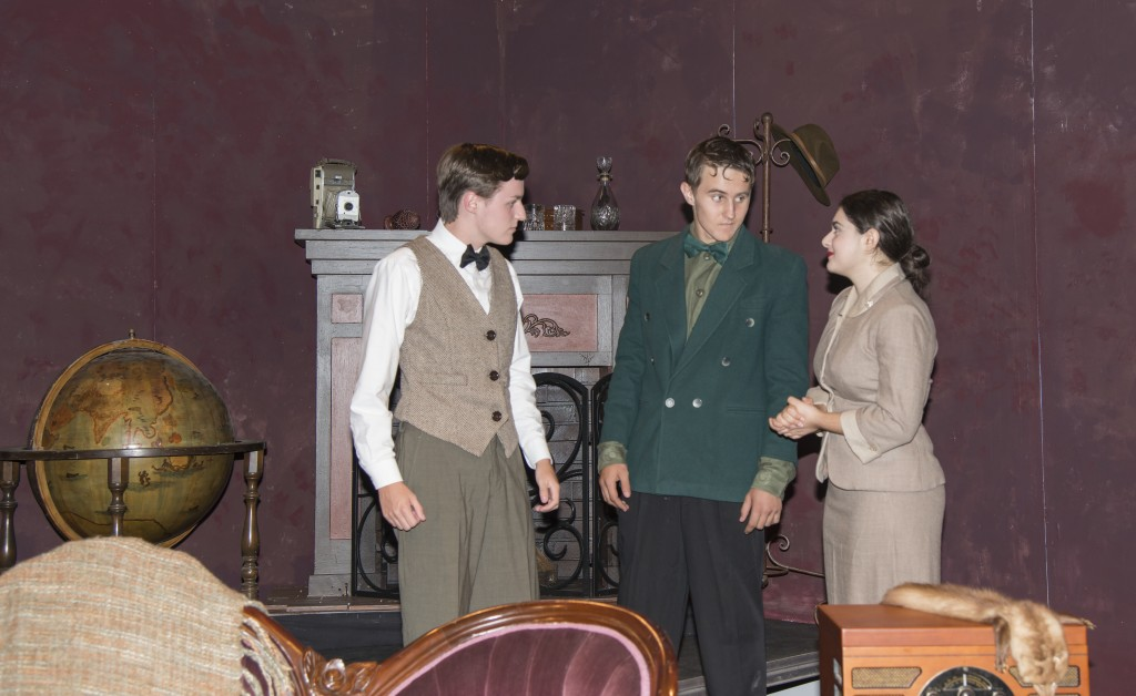 """(left to right) NHHS student director and actor Chris Surridge, a junior, and senior actors Race Chambers and Vita Muccia perform a scene from """"The Mousetrap."""" — Photo by Charles Weinberg"""