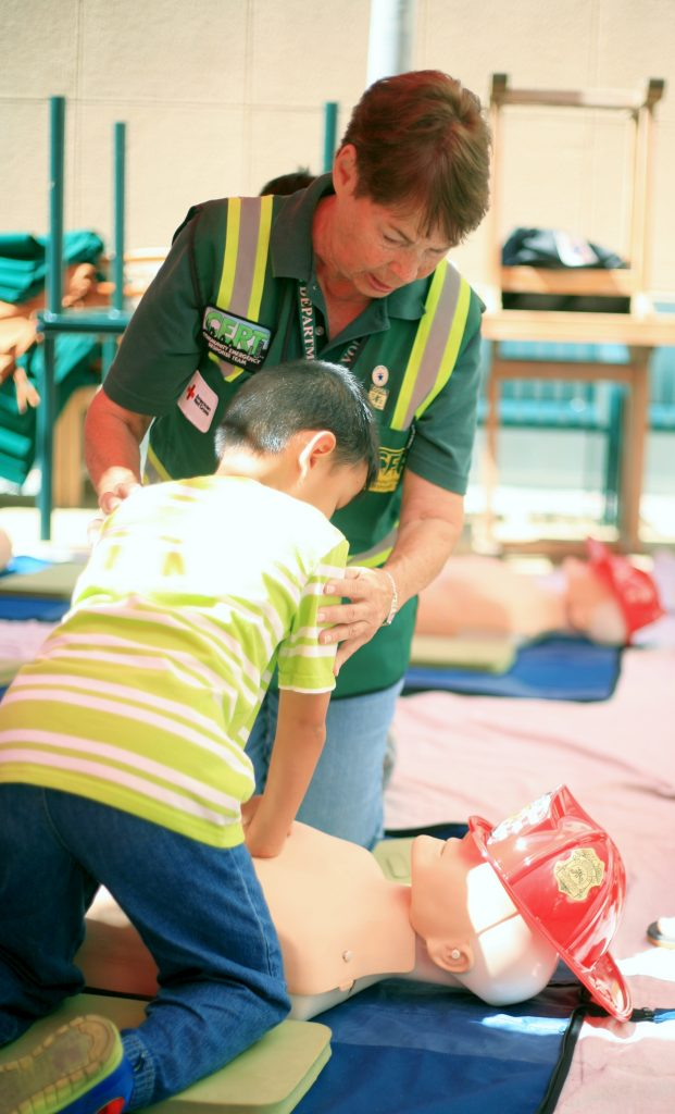 Newport Beach CERT volunteer Marilyn Broughton teaches Luther Nguyen, 7, of Garden Grove how to perform CPR during Saturday's Preparedness Expo. — Photo by Sara Hall ©
