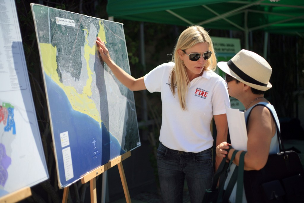 Newport Beach Emergency Services Coordinator Katie Eing explains the city's tsunami evacuation map to expo attendees.  — Photo by Sara Hall ©