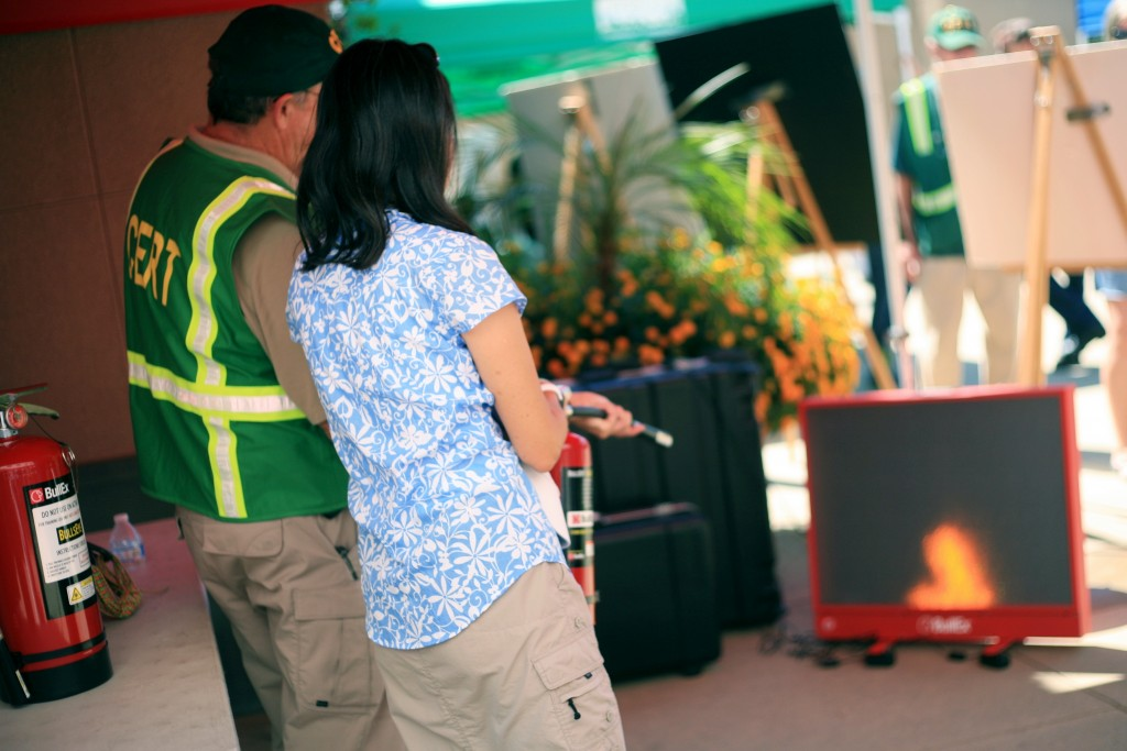 Laguna Beach CERT member Sonny Myers (left) helps Newport Beach resident Debbie Chan use an extinguisher to douse a digital fire at the expo. — Photo by Sara Hall ©