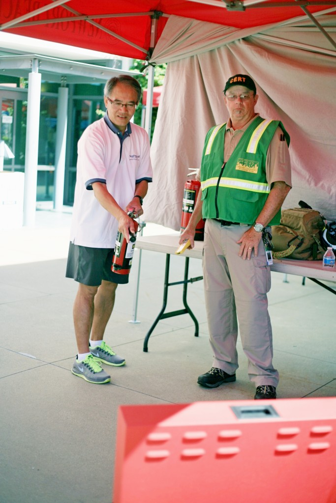 Laguna Beach CERT member Sonny Myers (right) helps Newport Beach resident Victer Chan use an extinguisher to douse a digital fire at the expo. — Photo by Sara Hall ©