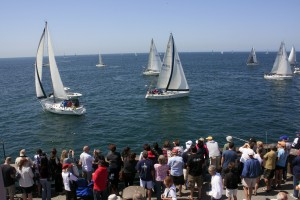 Locals and tourists crowd onto the Balboa Pier to watch the start of the Newport to Ensenada race