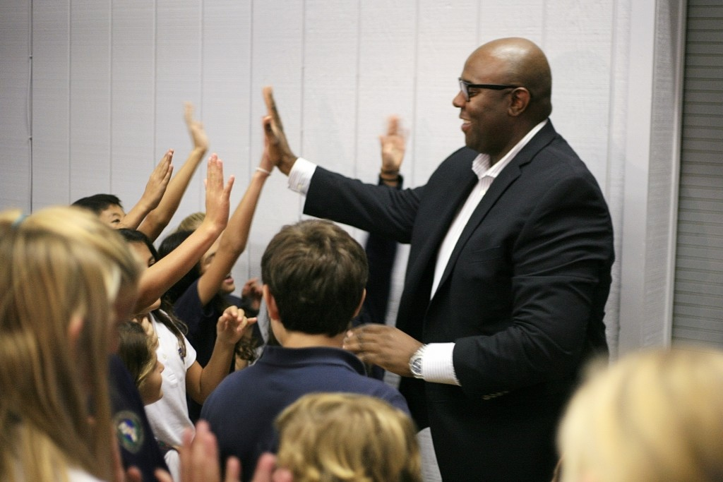 Retail expert Freddy Cameron gives high fives to Harbor Day students after the assembly. — Photo by Sara Hall ©