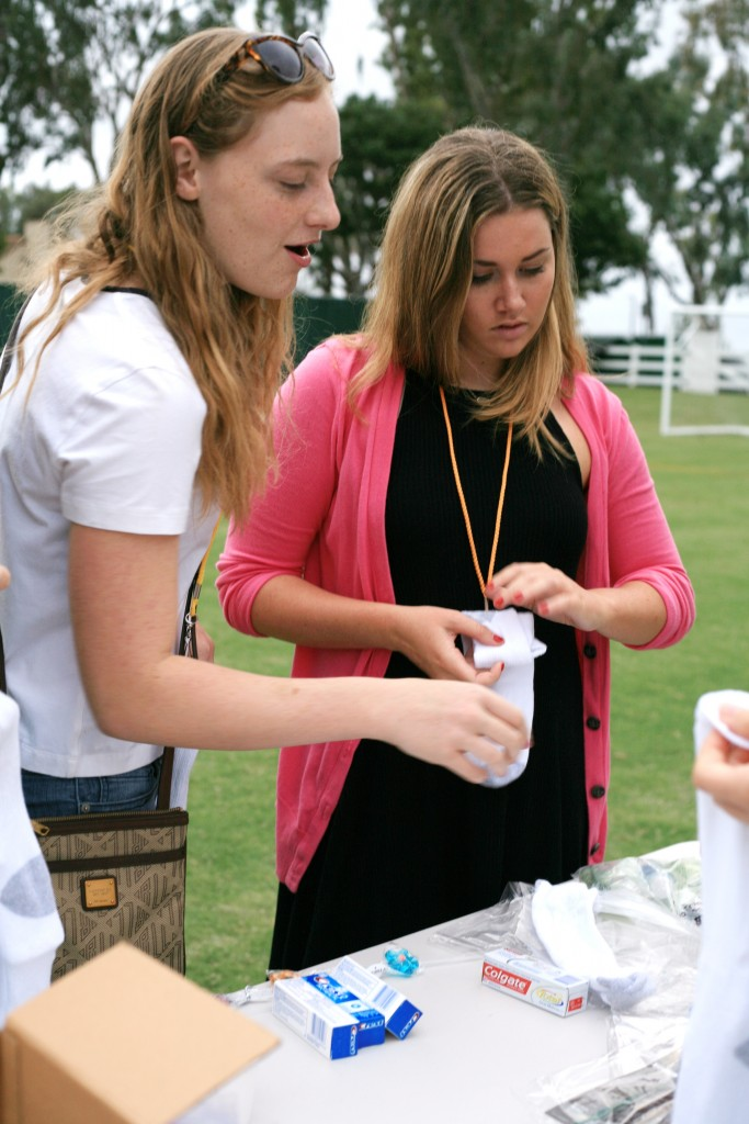 Corona del Mar seniors Claire Robertson (left) and Abigail Klein, both 17, create basic hygiene kits by filling socks with small items like toothpaste and soap. — Photo by Sara Hall ©
