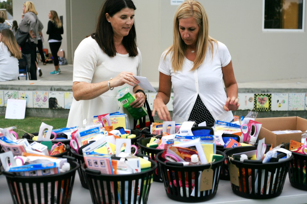 NCL moms (left) Chelle Wood, a philanthropy chair for the organization, and Stacy Peterson, the eighth grade level advisor, organize baskets full of donated items for Second Step. — Photo by Sara Hall ©