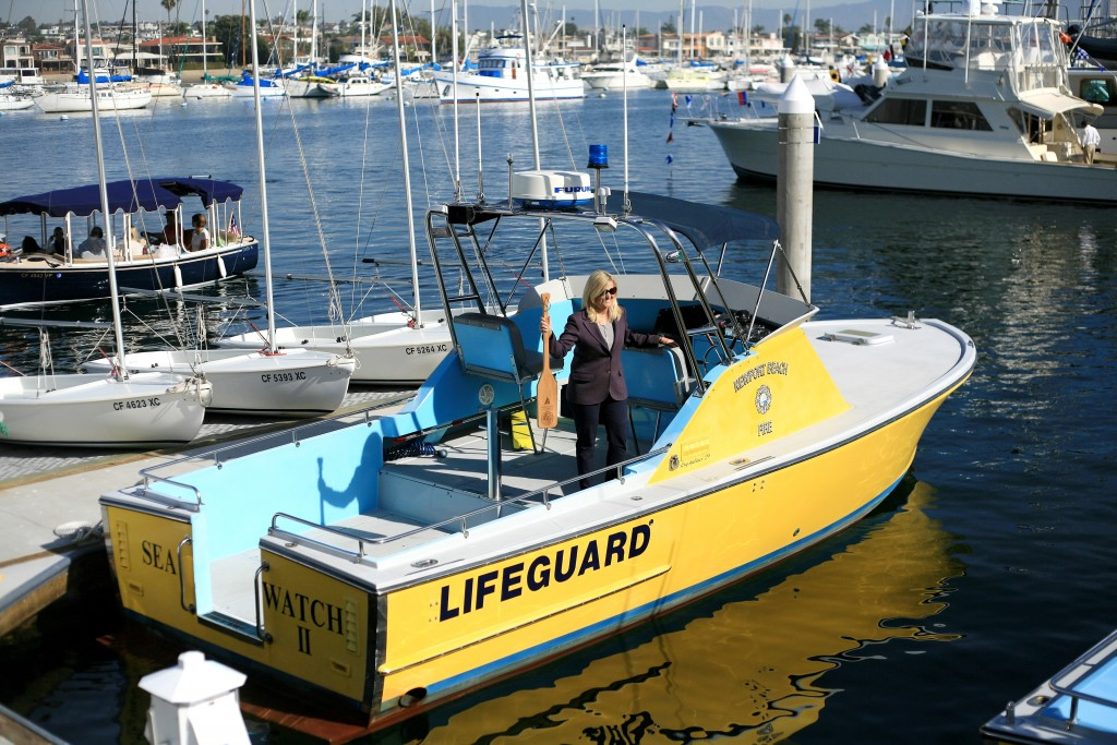 Former Newport Beach City Councilwoman Leslie Daigle poses for a photo on the NB lifeguard boat with a Marina Park commemorative oar. — Photo by Sara Hall ©