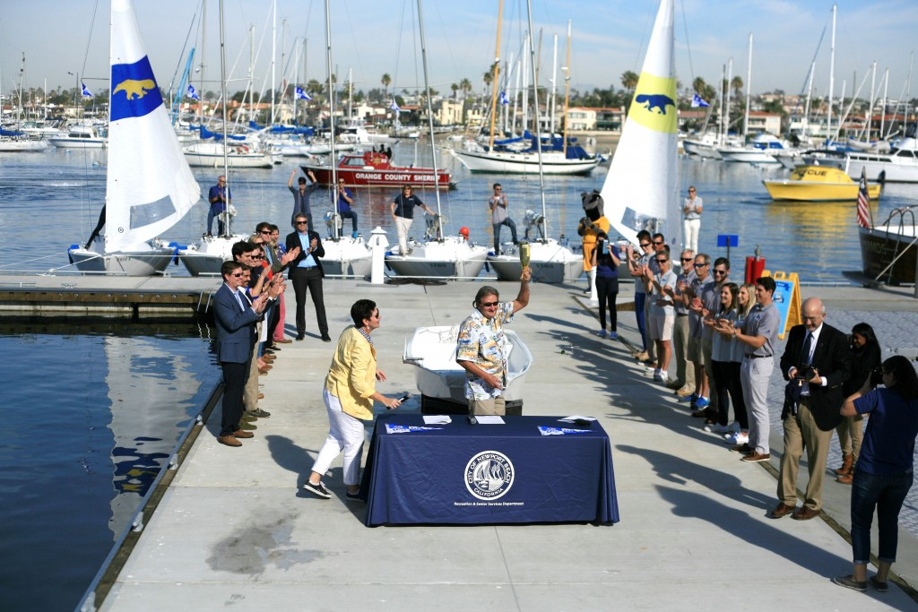 Councilman and Former Mayor Ed Selich holds up a broken champagne bottle after christening the fleet from the University of California, Irvine, sailing program. — Photo by Sara Hall ©