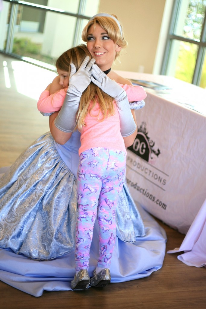 Caroline Corum, 4, gets a hug from Cinderella at the Marina Park event on Saturday. Her grandmother, Susan, lives on the peninsula. — Photo by Sara Hall ©