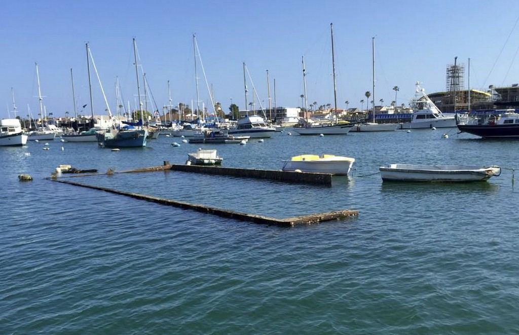 The top portion of the sunken Shellmaker, Inc., scow, Gemini, is still visible in Newport Harbor during low tide. It is scheduled to be removed within the next few weeks.  — Photo courtesy the city of Newport Beach ©