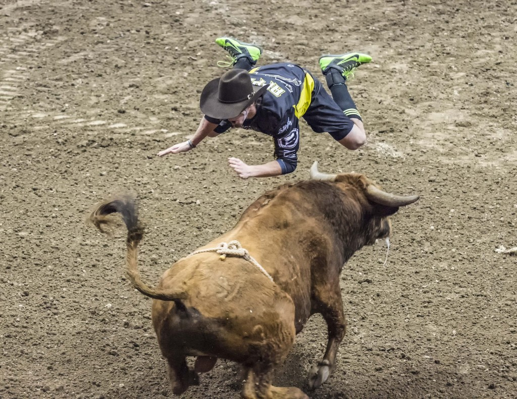 A PBR fighter flies over a bull during the event. — Photo by Lawrence Sherwin ©