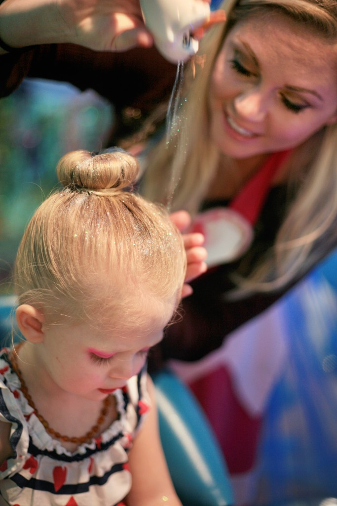 Berlin Martin, 2, gets glitter sprinkled into her hair by her mom, Gillian, in the Jellyfish Salon. — Photo by Sara Hall ©