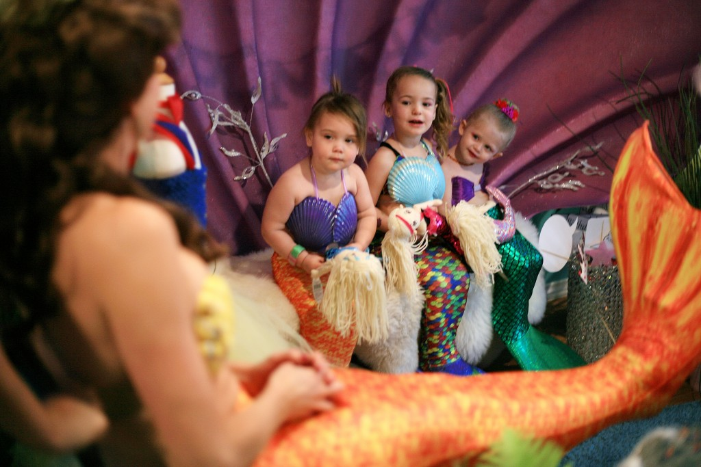 Mini mermaids (left to right) Madeline Unverferth, 2, Skylar Amirpur, 3, and Berlin Martin, 2, get excited as they see Princess Belle (transformed into a mermaid) come to visit. — Photo by Sara Hall ©
