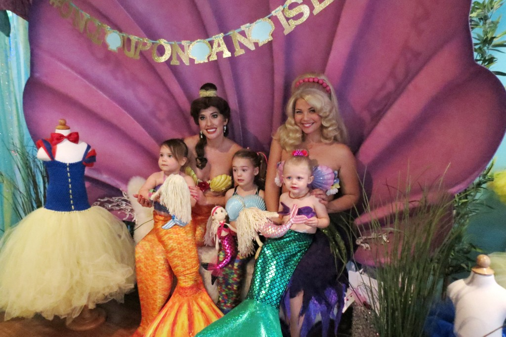 Mini mermaids (left to right) Madeline Unverferth, 2, Skylar Amirpur, 3, and Berlin Martin, 2, pose for photos with Princess Belle (transformed into a mermaid) and Arista mermaid. — Photo by Elizabeth Greenberg ©