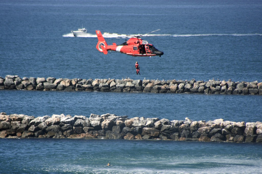 "A U.S. Coast Guard rescue diver and ""victim"" are pulled up to the helicopter as another ""victim"" waits in the water. — Photo by Sara Hall ©"