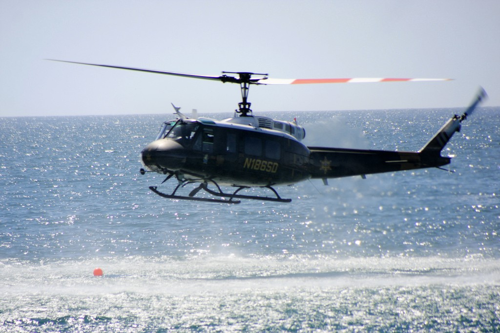 The Orange County Harbor Patrol helicopter hovers over the water during the disaster drill. — Photo by Sara Hall ©