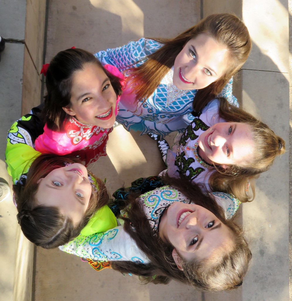 (clockwise, from top right in blue) Gillian Ippoliti, McKenna Walsh, Eva Stanton, Samantha Stoke, and Kaitlin Ryan from Anair Irish Dance School pose for a photo before performing. — Photo by Sara Hall ©