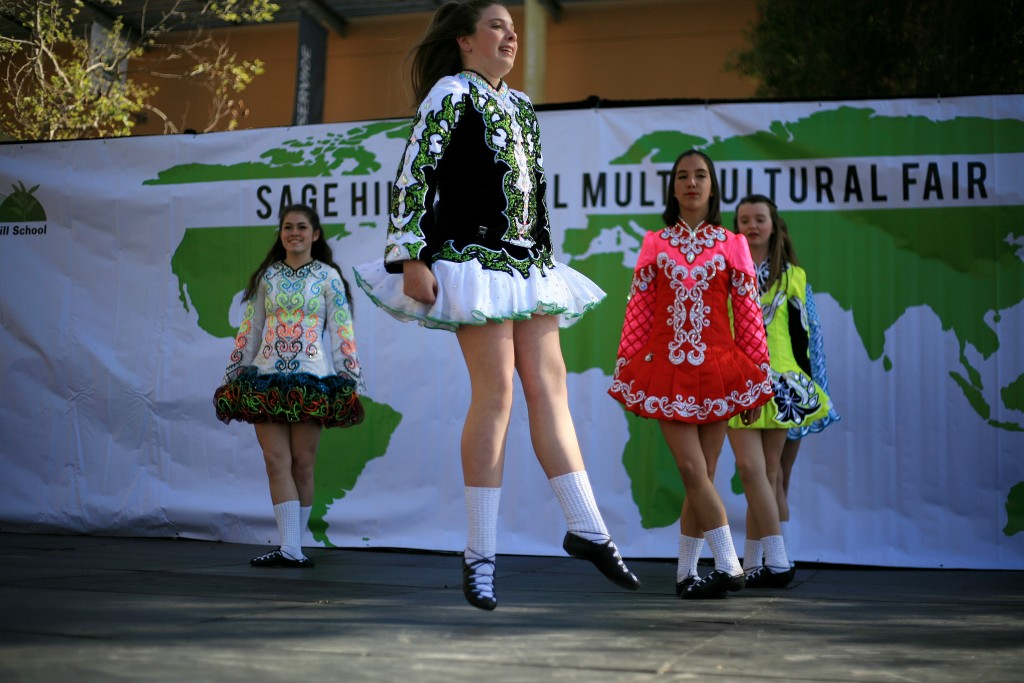 McKenna Walsh (front) leaps in the air while she and Kaitlin Ryan (front right), Samantha Stoke (back right), Eva Stanton (front left) and Gillian Ippoliti (hidden in back) from Anair Irish Dance School perform a traditional Irish dance. — Photo by Sara Hall ©
