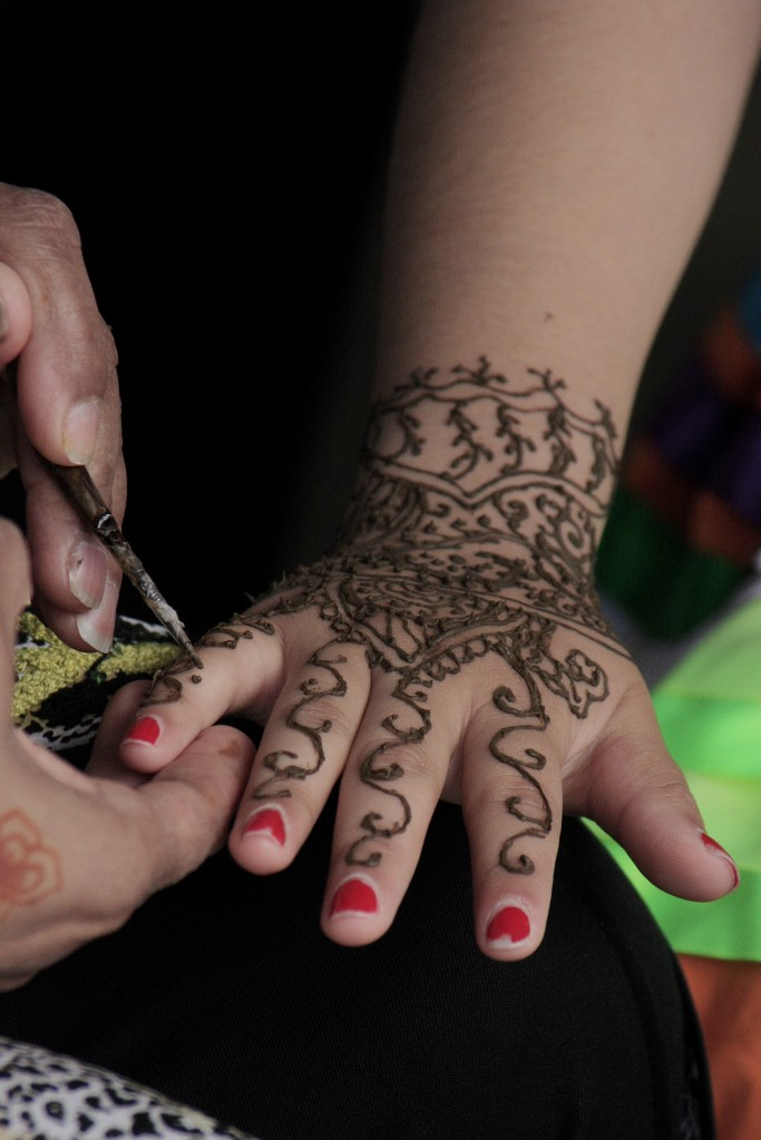 Rana Mohiuddin of Think Outside the Vase draws henna on the hand of Sage sophomore Genesis Gonzalez. — Photo by Sara Hall ©