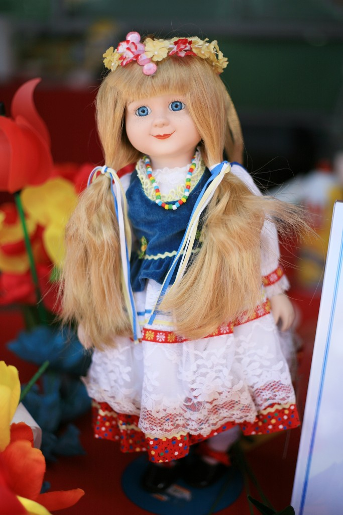 A doll dressed in traditional clothing decorates the Poland booth. — Photo by Sara Hall ©
