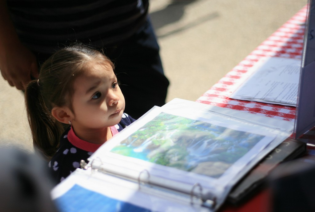 "Arianna Soto, 2, watches as her ""passport"" booklet gets stamped. Her aunt, Melissa Iglesias, is a senior at Sage Hill. — Photo by Sara Hall ©"