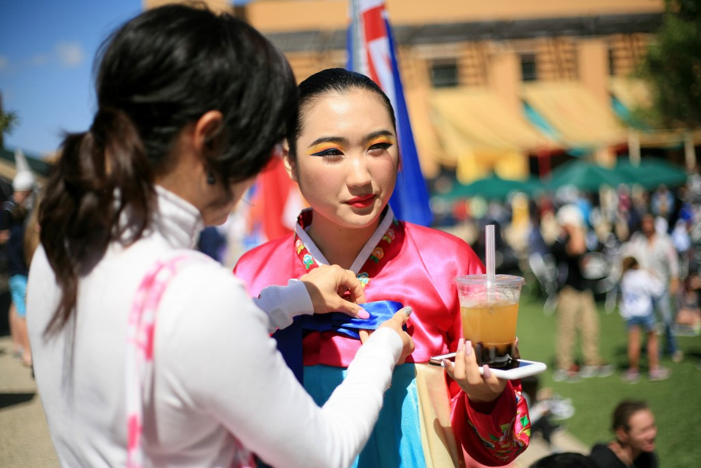 A Korean Nongak dancer from KAYPA gets her bow adjusted and enjoys a drink before heading on stage to perform. — Photo by Sara Hall ©