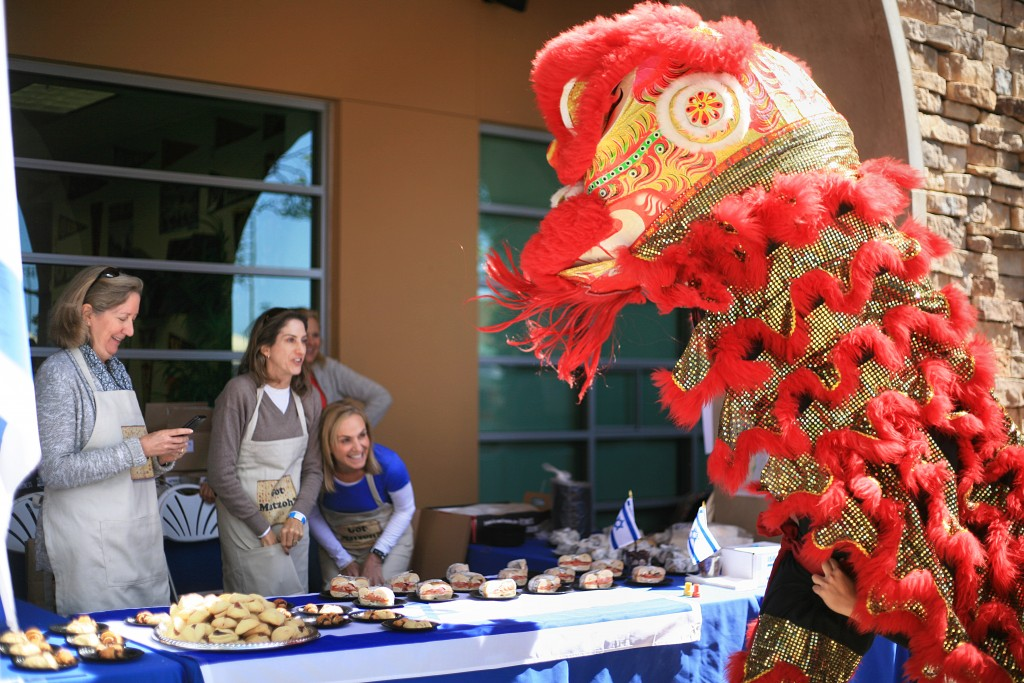 Traditional Chinese lion dancers from the Ane Thanh troupe check out a food booth while the parent volunteers laugh and take photos during the 15th Annual Sage Hill Multicultural Fair on Saturday. — Photo by Sara Hall ©