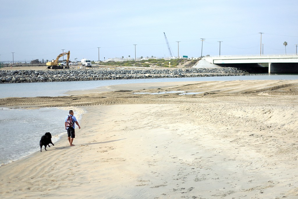 Dogs and people walk along the sand near the Santa Ana River mouth. — Photo by Sara Hall ©