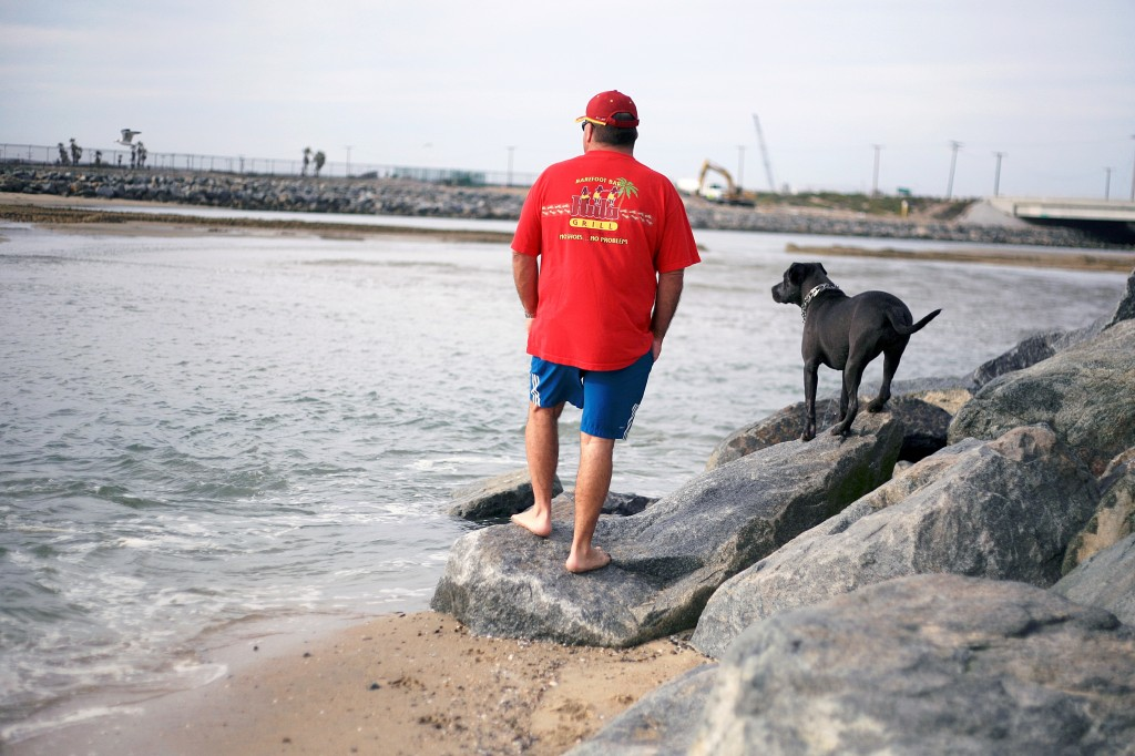 Newport Beach resident Robert Wyatt and his dog Stella, a 1-year-old rescued mixed breed pup, look out at the water from the beach near the Santa Ana River mouth on Thursday. — Photo by Sara Hall ©