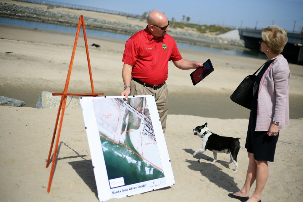 Tim Whitacre, representative for Orange County Board of Supervisors Vice Chair Michelle Steel, and Newport Beach Mayor Diane Dixon discuss the unofficial dog beach at the Santa Ana River mouth as an off leash dog runs by during a press conference on Saturday. — Photo by Sara Hall ©