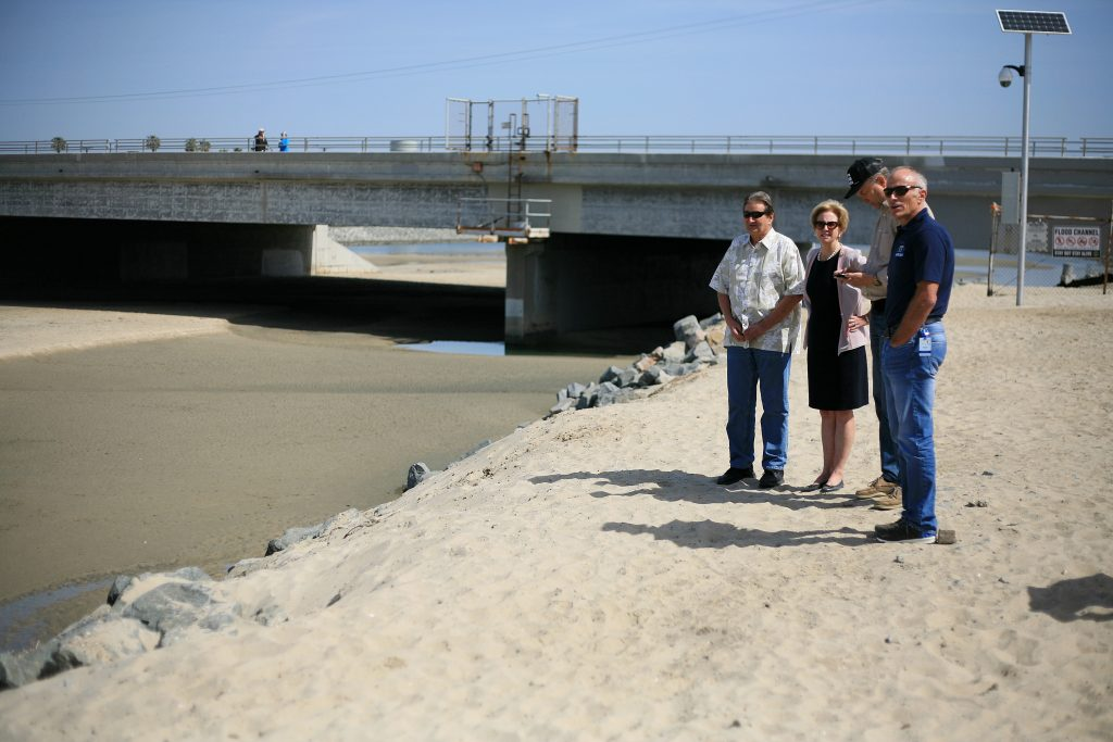(left to right) Beach Councilman Ed Selich, NB Mayor Diane Dixon, NB Councilman Scott Peotter, and NB City Manager Dave Kiff talk about the unofficial dog beach near the Santa Ana River mouth on Saturday. — Photo by Sara Hall ©