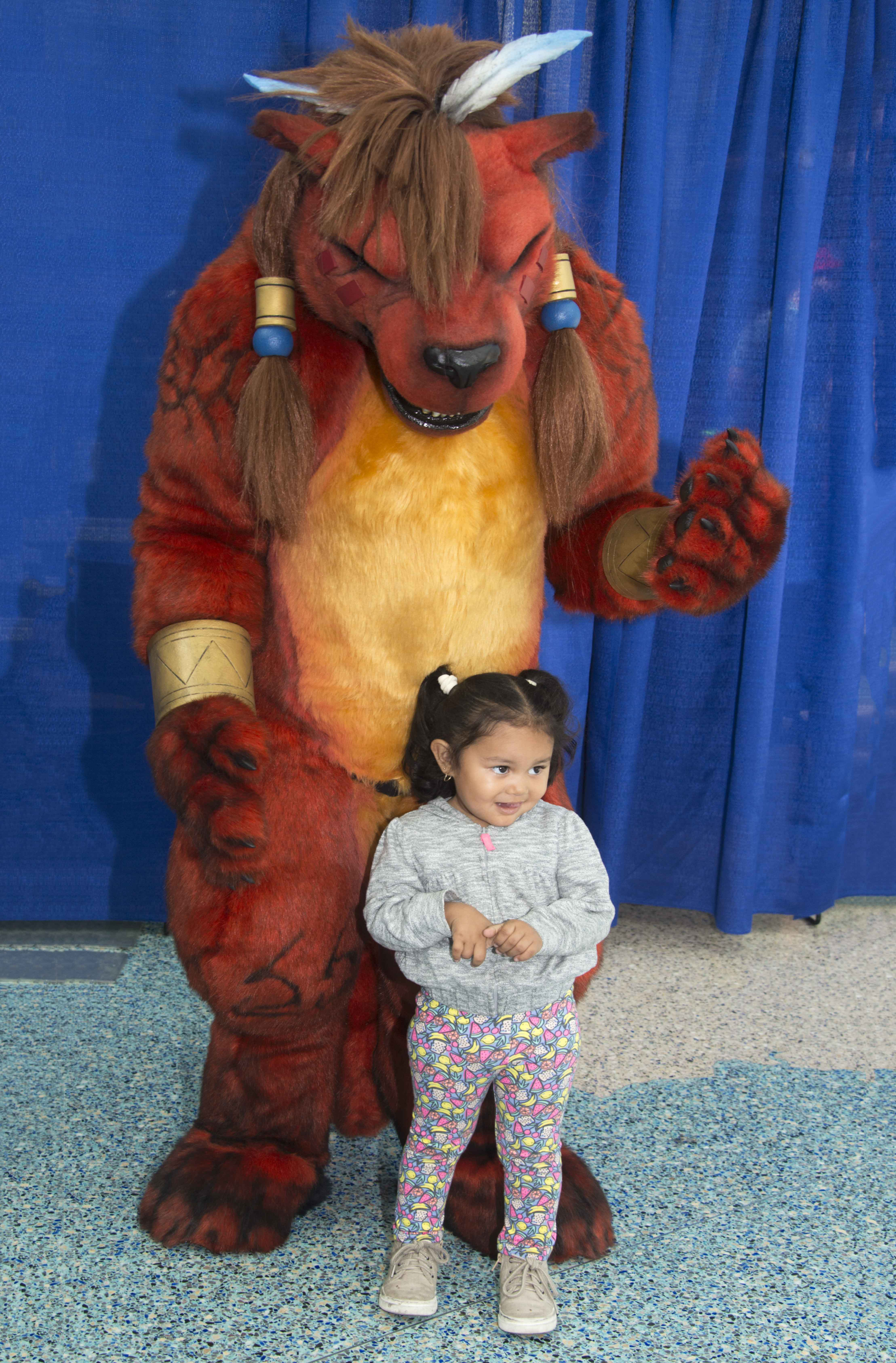 Red XIII, a character from Final Fantasy VII, poses for a photo with a child at WonderCon. — Photo by Lawrence Sherwin ©