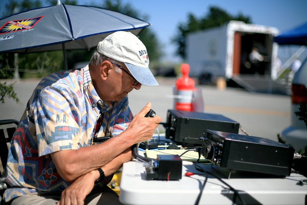 Newport Beach Radio Amateur Civil Emergency Service member Roy Shlemon talks on his ham radio Saturday during the American Radio Relay League Field Day event. The city's emergency services radio trailer can be seen set up in the background. — Photo by Sara Hall ©