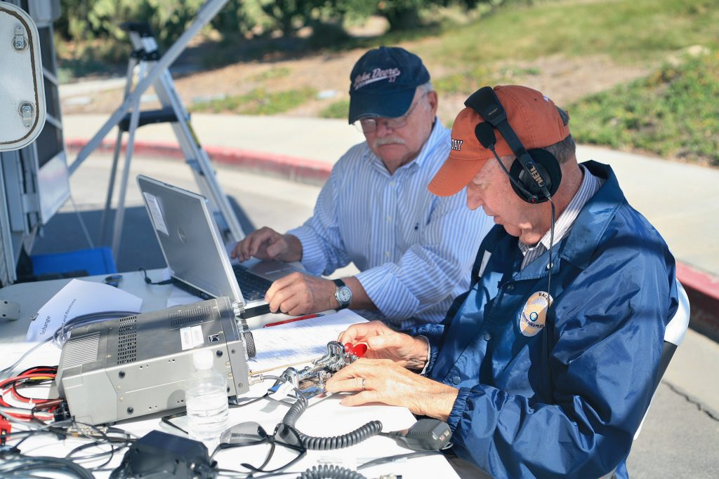RACES members Bob Carlson (front right) and Jack Buzzard send a Morse code message during ARRL Field Day on Saturday. — Photo by Sara Hall ©
