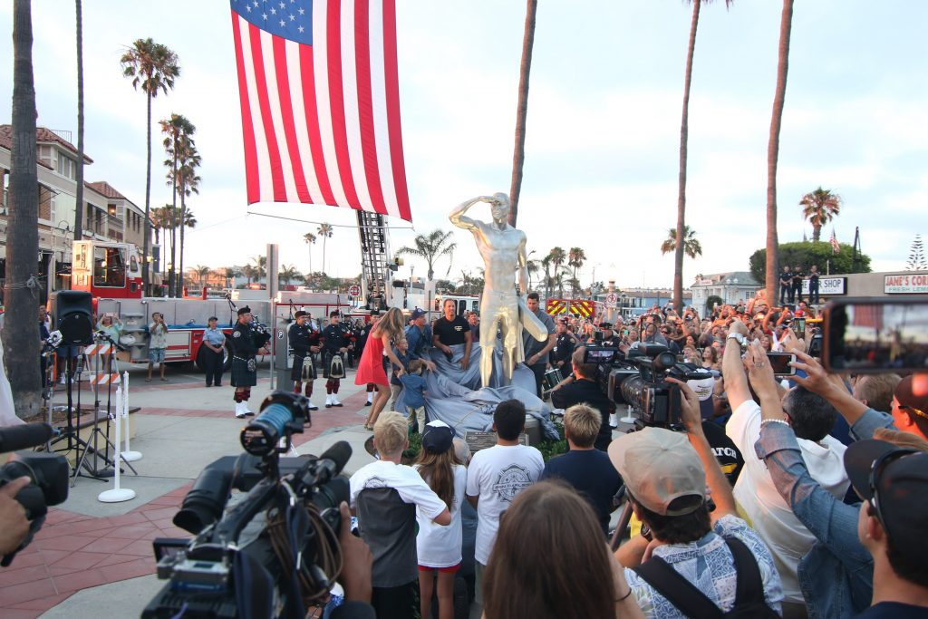 People cheer and take photos as friends and family members of Ben Carlson, the first Newport Beach lifeguard to die in the line of duty, is unveiled Wednesday night. — Photo by Jim Collins ©