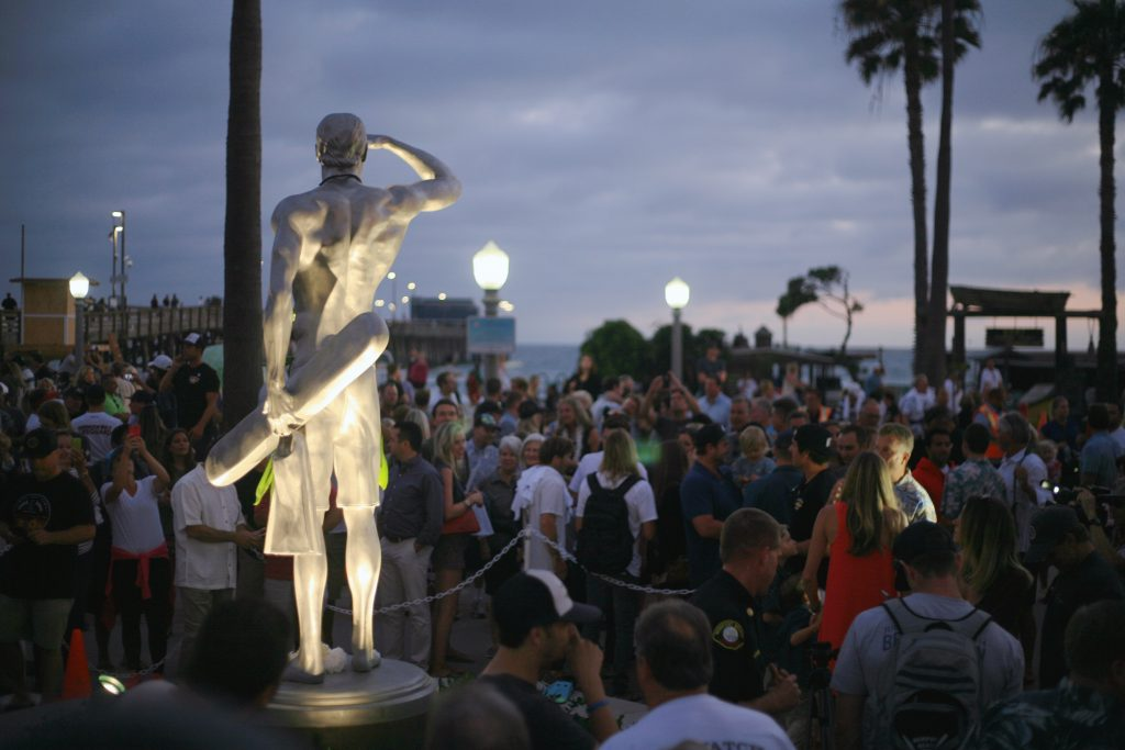 A statue depicting Ben Carlson, the first Newport Beach lifeguard to die in the line of duty, watches over the crowd and beach after an unveiling ceremony on Wednesday night. — Photo by Sara Hall ©