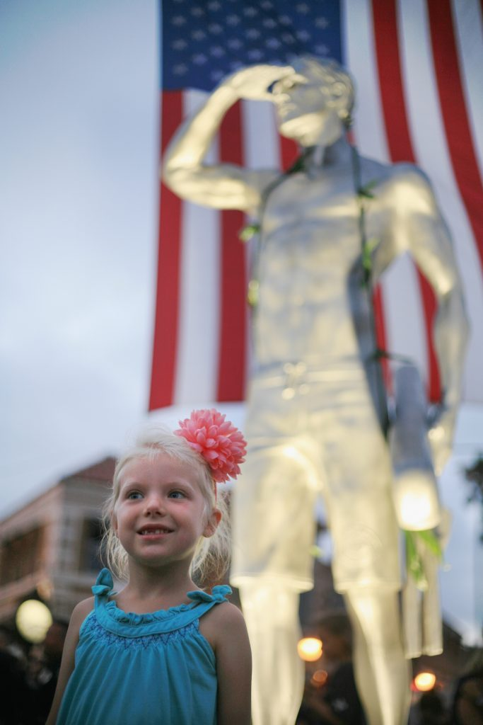 Grace Graham, 5, daughter of longtime Newport Beach lifeguard Chris Graham, poses for photos in front of the statue. — Photo by Sara Hall ©