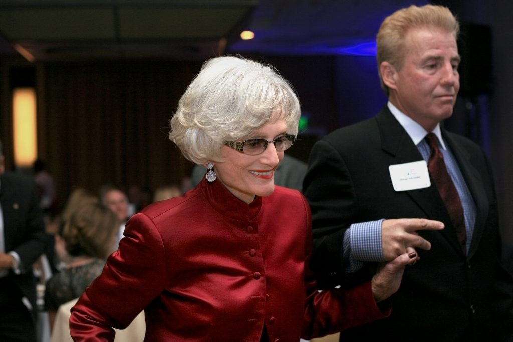 Marian Bergeson is escorted to the stage by George Schroeder to receive the SUNshine Award at Speak Up Newport's 33rd Mayor's Dinner in 2014. — Photo by Sara Hall ©