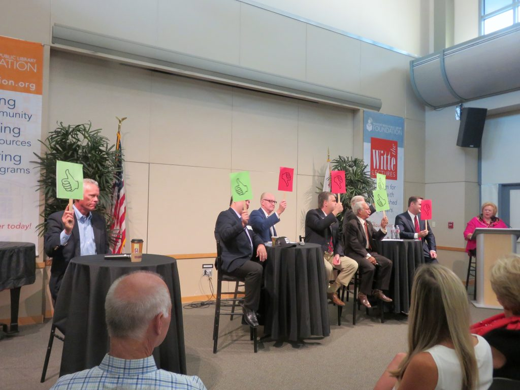 "(left to right) Brad Avery in District 2; Mike Glenn, Jeff Herdman, and Lee Lowrey for District 5; and Fred Ameri, Phil Greer (hidden slightly in background), and Will O'Neill for District 7, use""thumbs up"" or ""thumbs down"" paddles to answer a question asked by moderator Lucy Dunn at the NB Chamber candidate forum on Tuesday. — Photo by Sara Hall ©"