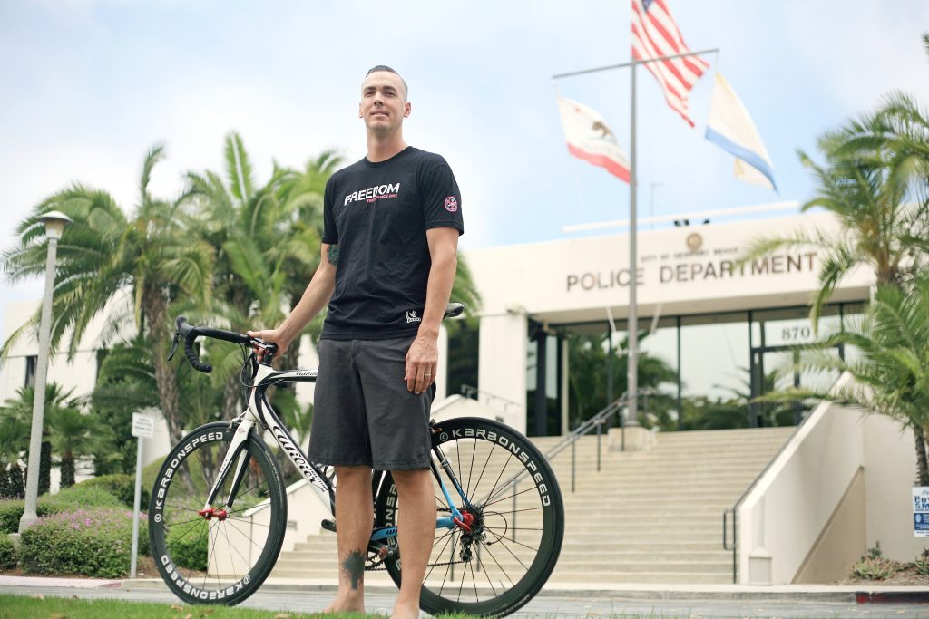 Newport Beach Police Department Detective Jason Prince poses with his bike in front of the NBPD station. Prince will be participating in the upcoming 1,500-mile Freedom Ride, which aims to raise awareness for human trafficking. — Photo by Sara Hall ©