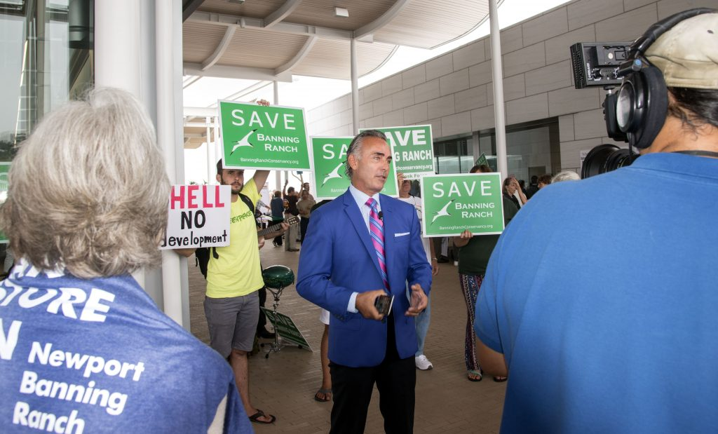 A Newport Banning Ranch project supporter talks to the press Wednesday as opponents wave signs behind him. — Photo by Charles Weinberg ©